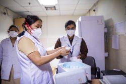 ニューデリーの病院でワクチン用保冷箱を確認する看護師。(インド、2021年2月15日撮影)