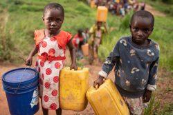 タンガニーカ州にある国内避難民の居住地の近くで、水を汲みに行く子どもたち。(2020年10月撮影)