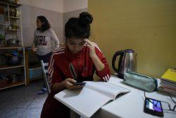 首都リマの自宅で宿題に取り組む15歳のダニエラさん。パソコンが自宅にないため、携帯アプリを通じて授業の映像を受信している。(ペルー、2020年9月撮影)