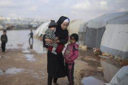 北西部にある避難民キャンプで浸水したテントの外に立つ家族。(2021年1月撮影)