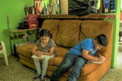 自宅で勉強ができるよう教育省から受け取った教材を使い、ソファの上で勉強する10歳のクリスティアンくんと、いとこで7歳のアリエルさん。(グアテマラ、2020年4月撮影)