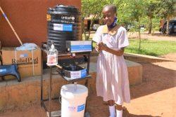 新しく小学校に設置された手洗い場で、正しい手洗いの方法について実演しながら説明する7年生の女の子。(ウガンダ、2020年12月撮影)