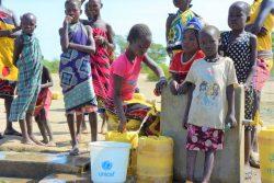 北部トゥルカナ郡の村でユニセフが支援する太陽光発電の給水所で、水を汲む女性と子どもたち。(ケニア、2020年2月撮影)