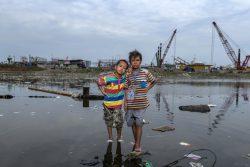 北ジャカルタで増水になった自宅近くの外に立つ7歳のサトリオくん(左)と9歳のアフメドくん(右)。(インドネシア、2020年9月撮影)