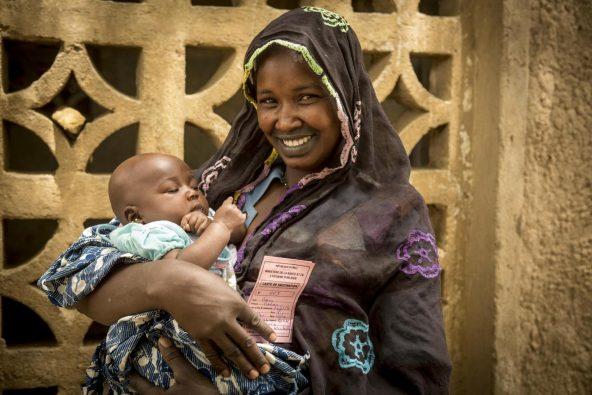 予防接種を受けたマリアムくん(生後3カ月)を笑顔で抱っこする母親のアイサタさん。