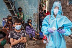 ムンバイのスラム街で、個人用防護具(PPE)を着用してCOVID-19の啓発活動を行う様子。(2020年6月撮影)