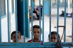ガザの一時避難所として使われているUNRWAの学校の門から外を除く子どもたち。(2021年5月15日撮影)