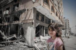 破壊されたガザ地区の建物の前で家族を待つ女の子。家族は、建物内にある自宅から持ち物を取り出している。(2021年5月17日撮影)