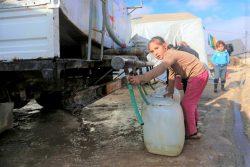 北西部のKafr Losin難民キャンプで、給水トラックから水を汲む女の子。(シリア、2021年1月撮影)