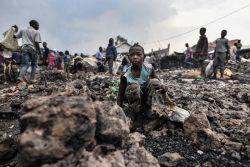 火山噴火によって流れ出た溶岩が散乱する場所で座る子ども。(2021年5月23日撮影)