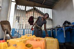 ゴマのバイパス配管システムによって供給された水を、水タンクに汲む女の子。(2021年6月4日撮影)