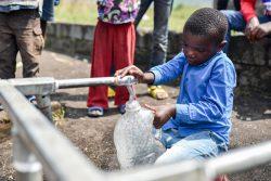 北キブ州・サケでユニセフが支援する折りたたみ式水タンクから水を汲む子ども。(2021年6月2日撮影)