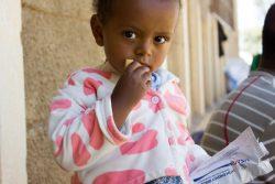 ティグライ州都メケレにある国内避難民キャンプで、高カロリービスケットを口にする2歳のメクリットちゃん。(2021年2月撮影)
