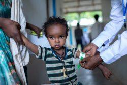 上腕計測メジャーを使って栄養不良の検査を受ける下痢性疾患のある1歳のメセレトちゃん。(エチオピア、2021年6月7日撮影)