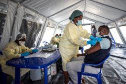 北キブ州・ゴマの州立病院にある予防接種用テントの中で、COVID-19の予防接種をする医療従事者。(コンゴ民主共和国、2021年5月撮影)