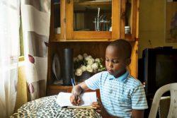 自宅で宿題をするカレブくん(10歳)。学校授業はラジオやテレビで放送されるが、その授業の前に、お姉ちゃんとノートを見せ合って予習している。(ルワンダ、2020年5月撮影)