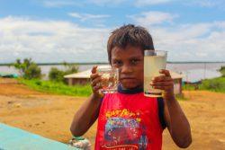 ボリバル州で、2つのコップを手に持つ子ども。新しく設置された水タンクの水(左)と、設置以前に飲んでいた川の水(右)がそれぞれ入っている。(ベネズエラ、2020年7月撮影)