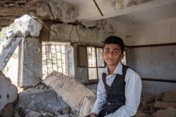 ハッジャ県にある破壊された学校の中で、瓦礫の上に座る12歳のアフメドくん。(2021年3月撮影)