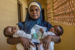 バウチにあるプライマリ・ヘルスセンターで、双子の赤ちゃんの出生証明書を持つ母親。(ナイジェリア、2020年10月撮影)