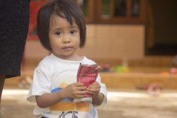 東ヌサ・トゥンガラ州の自宅で、すぐに食べられる栄養治療食(RUTF)を手に持つ、重度の消耗症と診断された1歳のフェリシティちゃん。(インドネシア、2021年2月撮影)