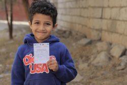 コレラの予防接種を受けた証明書を手に持つ7歳のファドルくん。(イエメン、2021年2月撮影)