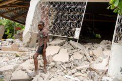 崩壊した建物の側に立つ10歳のアンドレくん。(2021年8月16日撮影)