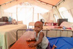 仮設避難所となっているレカイの高校で、ユニセフが支援するテントの中に座る1歳のカールちゃん。(2021年8月17日撮影)