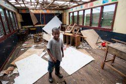サイクロンの被害を受けた教室に立つ男の子。(フィジー、2021年1月撮影)