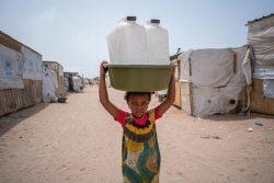 国内避難民キャンプで、水容器などの支援物資を受け取った7歳のリームさん。(イエメン、2021年6月撮影)