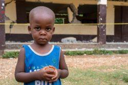 地震で崩れた校舎の前に立つ男の子。(2021年9月3日撮影)
