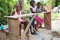 レカイ(Les Cayes)東部にある、地震の被害を受けた学校の隣のベンチに座る女の子たち。(2021年8月30日撮影)