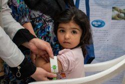 ヘラートの保健センターで、上腕計測メジャーを使って栄養不良の検査を受ける2歳のファティマちゃん。(2021年8月30日撮影)
