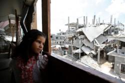 空爆で破壊された自宅から外を眺める少女。