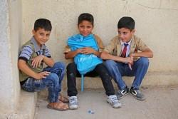 1カ月の補習授業の終了をお祝いするセレモニーに参加した、ユニセフの通学かばんを手にする国内避難民の男の子たち。