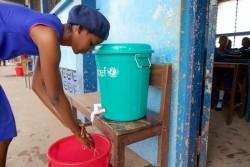 エボラの感染を予防するため、教室に入る前に手を洗う少女。