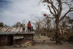 サイクロンの被害を受けた建物の屋根に立つ人々。(バヌアツ)