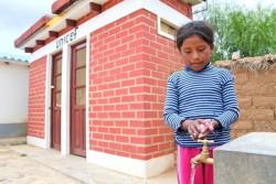 小学校のトイレで手を洗う9歳の女の子。