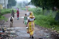 水を汲む容器を持って屋外に排泄に向かう女性。