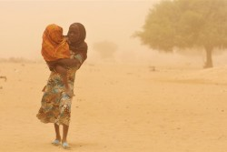 砂煙の中、幼い妹を抱えて歩くチャドの女の子。