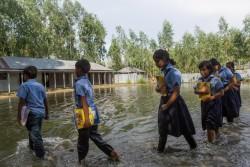 洪水の水が引かない中、学校に登校する生徒たち。