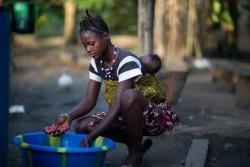 生後半年の赤ちゃんをおんぶして洗濯をする15歳の少女。