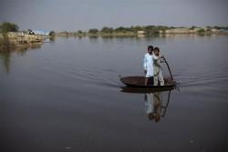 洪水の水が引かない中、大きな鍋を使って移動する子ども。(パキスタン、2011年撮影)
