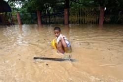洪水の水が引かないなか、荷物を抱えて歩く男の子