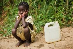 給水タンクの横で座る女の子。