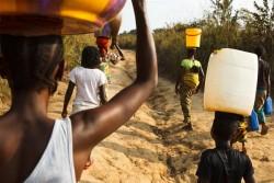 頭に水を入れたバケツを乗せ、自宅に戻る人々。