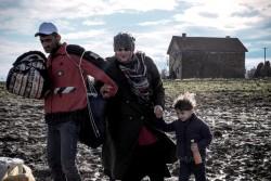 家族と手を繋ぎながらぬかるんだ道を歩くシリア難民の男性。