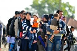 子どもを抱え、難民一時受け入れ所へ入る列に並ぶ人々。(マケドニア旧ユーゴスラビア共和国)