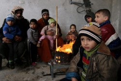 ガザ地区の破壊された自宅で、家族と一緒に焚火の周りに集まって暖を取る子どもたち。