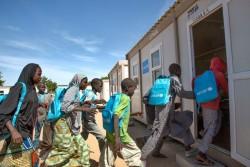国内避難民キャンプにある学校で、ユニセフの支援物資の通学かばんを身につけて教室に入る子どもたち。