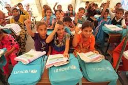 ユニセフのテントの仮設学校で、夏の補習授業を実施。先生の質問に手を挙げて答える国内避難民の子どもたち。(イラク)